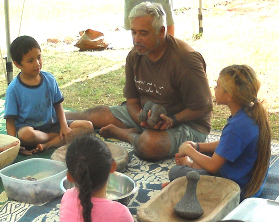 Eric Enos spends time with children to explain some of Hawaii's historical roots.