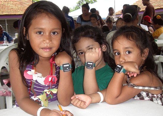 Three Head Start students from Aua Elementary School proudly display their newly attached wrist accelerometers. The girls will wear these over the next six days in order to CHL to record their physical activity levels and sleep patterns.