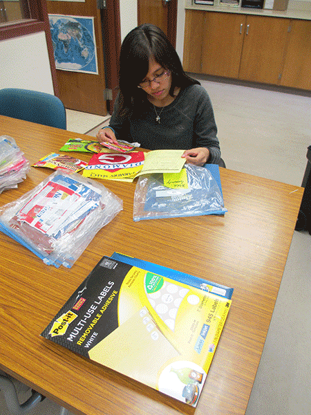 Guam CHL assistant Serena Cruz reviews food labels with the Food and Activity Log for data entry.