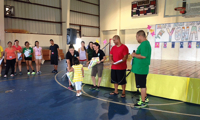 Yona summer camper receives her certificate on the final day of camp from members of the University of Guam (EFNEP and CHL) and Yona Mayor, Ken Joe Ada.