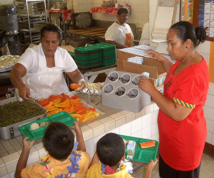 Trained food handlers serve children their lunch.