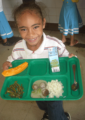 A happy young lady has been served a nutritious meal at her school.