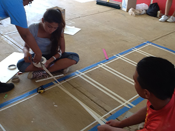Student volunteers measuring and preparing for the outline of one of the hopscotch designs.