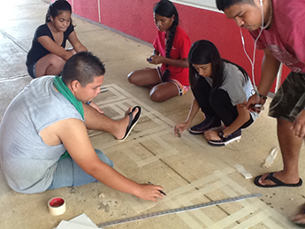 A group of student volunteers prepping for the outline of one of the hopscotch designs.