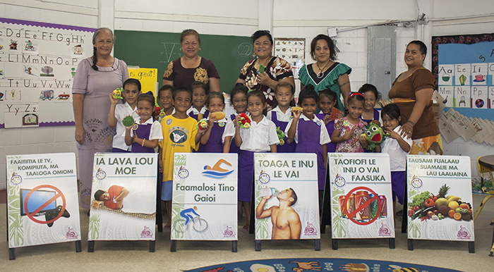 January 14, 2014: Aua Elementary School, American Samoa.  The CHL staff has just completed a nutritional training workshop with the children and teachers. These fun learning activities include stories, puppets, creating healthy food plates, singing and more. The six CHL message sandwich boards (Samoan version) are visible in front of the class photos.  (Photo by Dan Helsham, CNR Media Specialist).