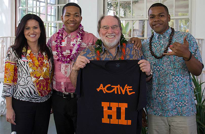Gov. Neil Abercrombie is presented with an ActiveHI T-shirt by Cedric (in red shirt) and Ben (with shaka sign) along with ActiveHI supporter City Council Member Kymberly Marcos Pine.