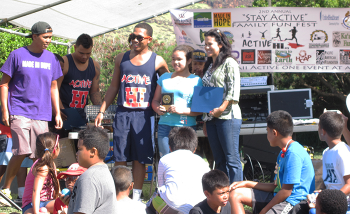At the Family Fun Fest, Cedric and Council Member Kymberly Marcos Pine pose with one of the 7 students selected to receive Active Hawaii Organization's 2013 Outstanding Student Award.