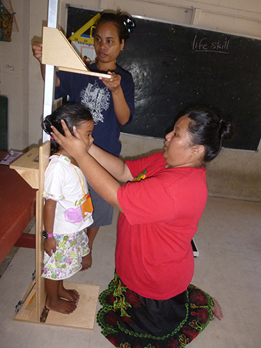 Joeleen Riklon; Outreach Educator RMI as well as Donna Lagbon, RMI Local Staff measure the height of this young lady in Ailinglaplap.